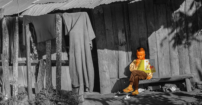 Lonely child outside house in shantytown